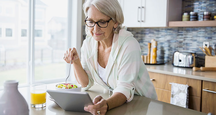Woman using a tablet device while eating breakfast.