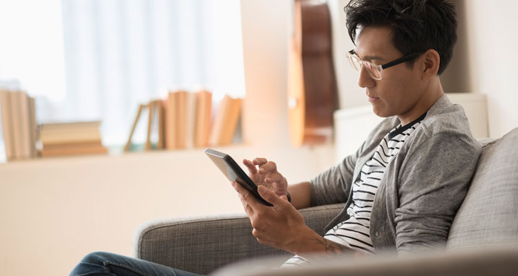Man looking at tablet device sitting on a couch